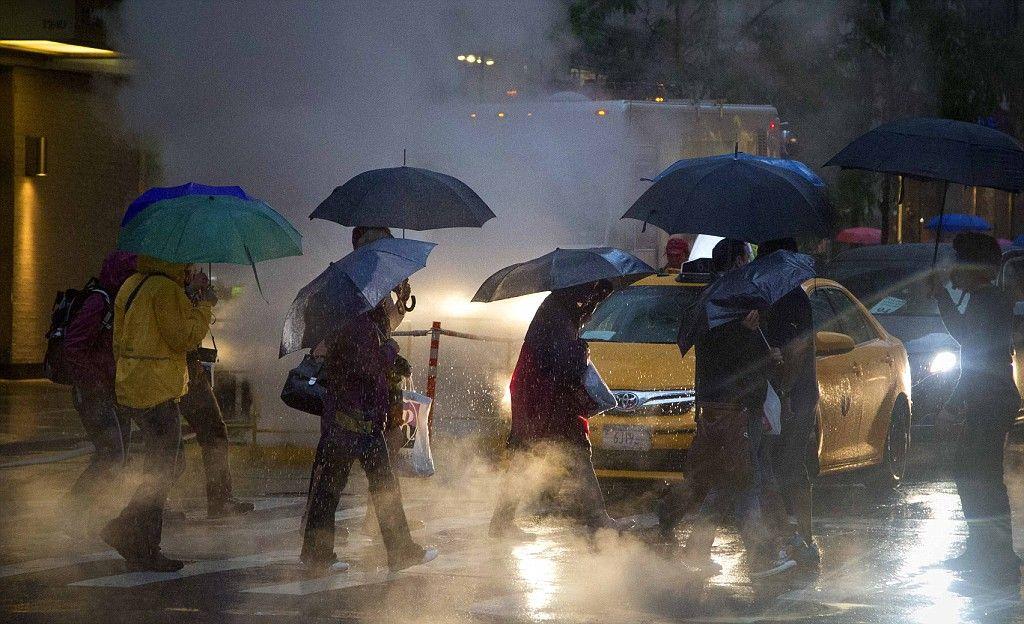 People walk down Sixth Avenue as heavy rain falls in New York